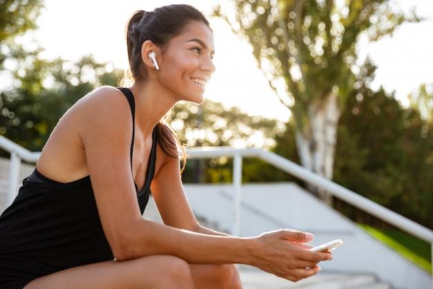 Retrato de uma mulher feliz fitness em fones de ouvido Foto gratuita
