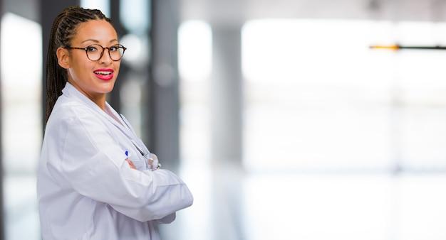 Retrato de uma mulher jovem médico negro, cruzando os braços, sorrindo e feliz, sendo confiante e amigável Foto Premium