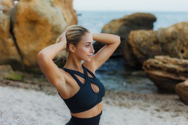 Retrato de uma mulher loira atraente no sportswear em uma praia selvagem. treino ao ar livre Foto Premium