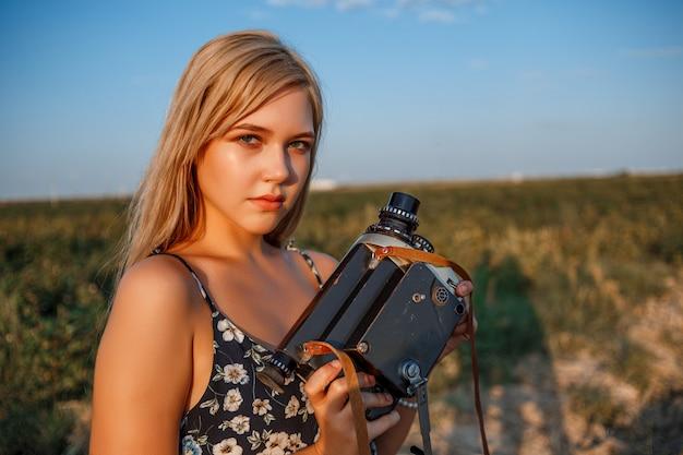 Retrato de uma mulher loira de vestido estampado floral com câmera de vídeo vintage no campo de uva durante o pôr do sol Foto Premium