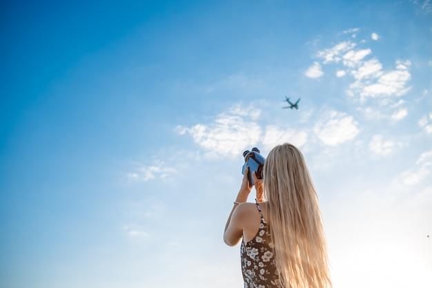 Retrato de uma mulher loira em um vestido estampado floral com uma câmera de vídeo vintage em um campo de uva grava vídeo de um avião decolando Foto Premium