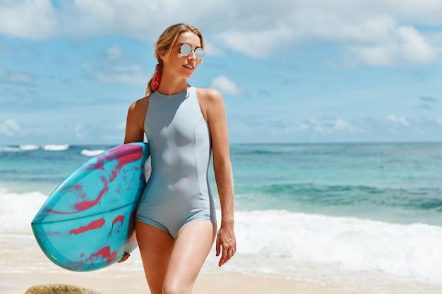 Retrato de uma mulher magra em maiô azul e óculos de sol da moda gosta de um dia de sol na praia do oceano, gosta de surfar, carrega prancha de surfe, aguarda vento para praticar esportes nas ondas Foto gratuita