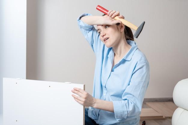 Retrato de uma mulher morena cansada com um martelo nas mãos, enxuga a testa com suor Foto Premium