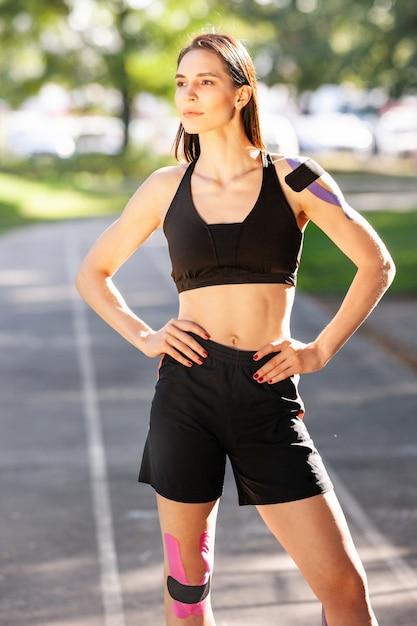 Retrato de uma mulher morena musculosa deslumbrante, vestindo roupa esportiva preta, posando ao ar livre Foto Premium