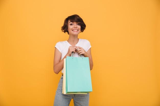 Retrato de uma mulher satisfeita sorridente segurando sacolas de compras Foto gratuita