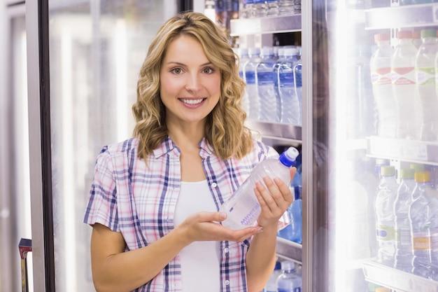 Retrato de uma mulher sorridente bastante loira tomando uma garrafa de água Foto Premium