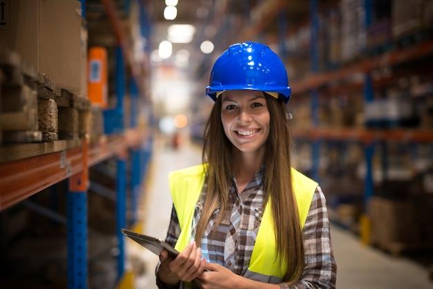 Retrato de uma mulher sorridente com uniforme de proteção e capacete segurando o tablet no centro do armazém Foto gratuita