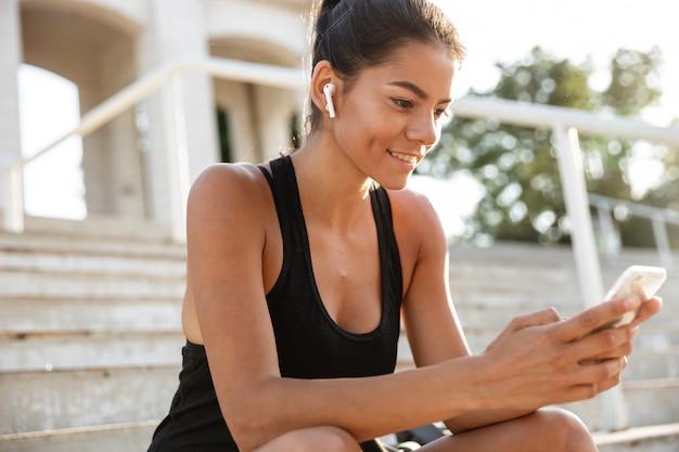 Retrato de uma mulher sorridente de aptidão em fones de ouvido Foto gratuita