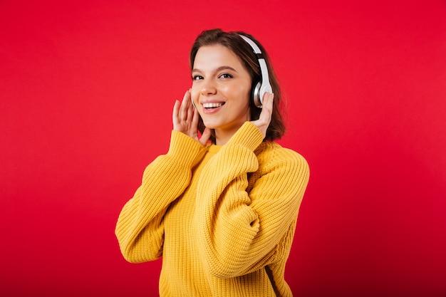 Retrato de uma mulher sorridente em fones de ouvido Foto gratuita
