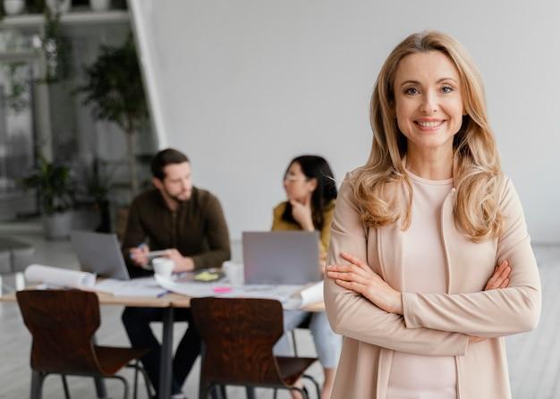 Retrato de uma mulher sorridente posando ao lado de seus colegas Foto gratuita