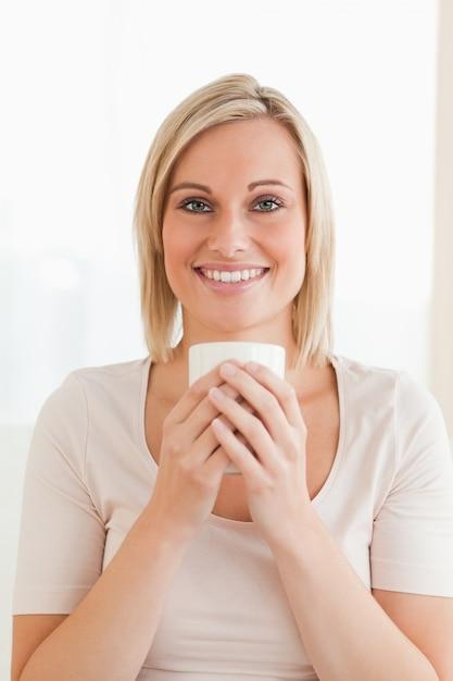 aa142f5e1 Retrato de uma mulher sorridente segurando uma xícara de café ...
