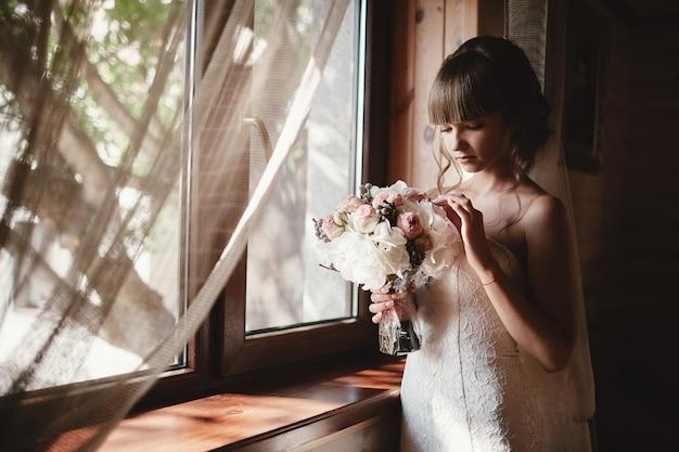 Retrato de uma noiva linda com um buquê de rosas e hortênsia interior. noiva muito feliz num vestido de luxo perto da janela. preparação da manhã do casamento Foto Premium