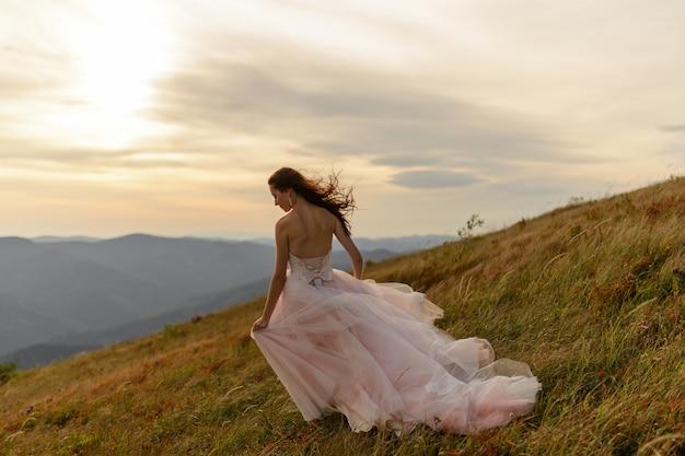 Retrato de uma noiva linda em um fundo de montanhas de outono. um vento forte sopra seu cabelo e vestido. cerimônia de casamento no topo da montanha. espaço livre. Foto Premium