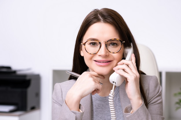 Retrato de uma senhora alegre moderna de óculos, segurando uma caneta e atendendo uma ligação enquanto trabalhava no escritório Foto Premium