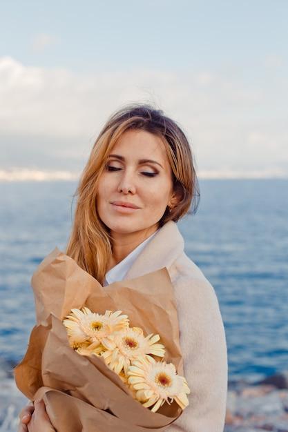 Retrato de uma senhora linda em pé e imaginando algo à beira-mar durante o dia. Foto gratuita