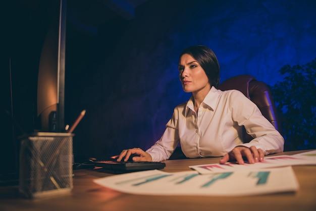 Retrato de uma senhora simpática, atraente e habilidosa, gerente de topo preparando relatório dinheiro salário proporção de moeda resultado juros investir analisando conta de auditoria econômica à noite escura estação de trabalho Foto Premium