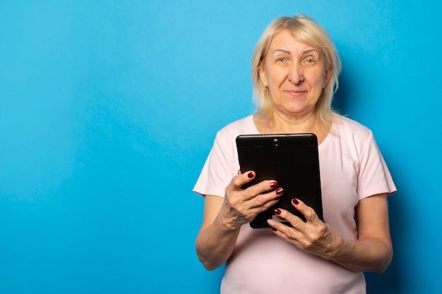 Retrato de uma velha amigável em uma camiseta casual, segurando um tablet nas mãos e olhando para a tela em uma parede azul isolada. rosto emocional Foto Premium
