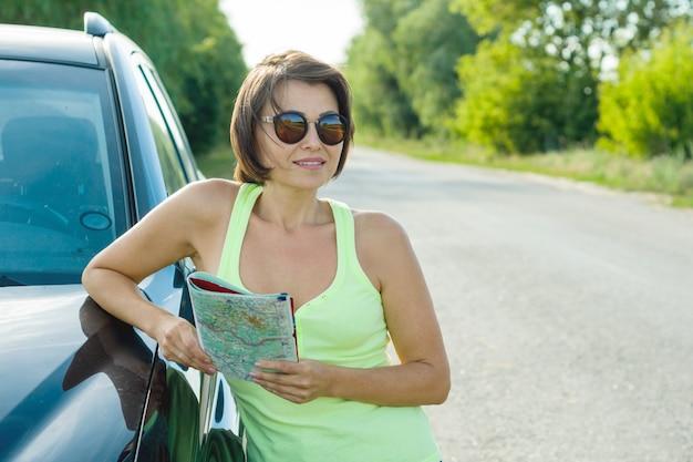 Retrato de verão ao ar livre de mulher madura com mapa Foto Premium