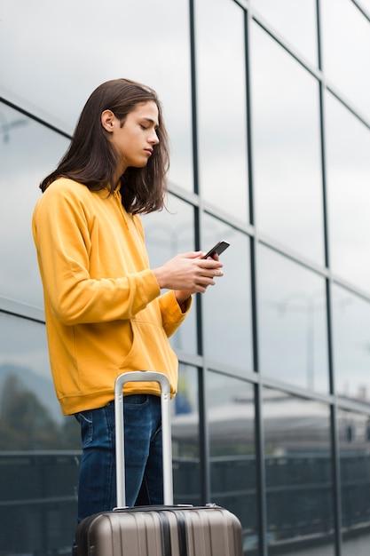 Retrato de viajante, verificando seu telefone Foto gratuita