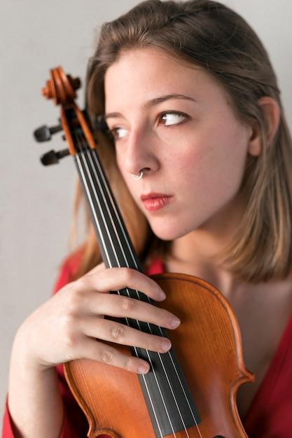 Retrato de violinista feminina com violino Foto gratuita