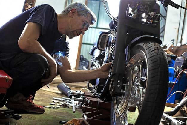 Retrato de vista lateral do homem que trabalha na garagem, reparação de moto Foto Premium