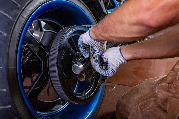 Retrato de vista lateral do homem que trabalha na garagem, reparando a motocicleta. as mãos fecham Foto Premium