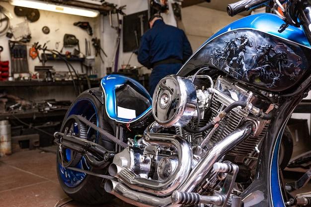 Retrato de vista lateral do homem trabalhando na garagem, reparando a motocicleta e personalizando-o Foto Premium