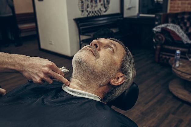 Retrato de vista lateral perfil close-up de bonito caucasiano barbudo homem ficando barba aliciamento na barbearia moderna. Foto gratuita