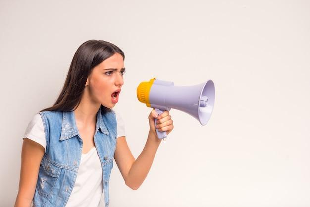 Retrato do adolescente alegre da menina, gritando em um megafone. Foto Premium