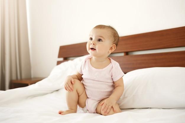 Retrato do bebê recém-nascido agradável bonito bonito na camisa cor-de-rosa que senta-se na cama em casa. Foto gratuita