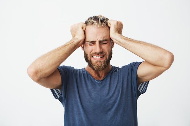 Retrato do belo cara nórdico com corte de cabelo na moda e barba segurando a cabeça com as mãos, sofrendo de dor de cabeça Foto gratuita