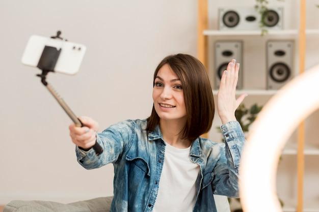 Retrato do blogueiro se filmando em casa Foto gratuita