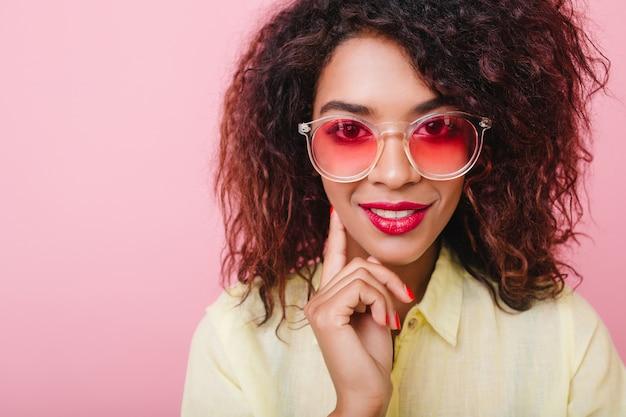 Retrato do close-up da garota sensual interessada em óculos rosa, tocando a bochecha com a mão. senhora adorável com pele morena e maquiagem brilhante sorrindo. Foto gratuita