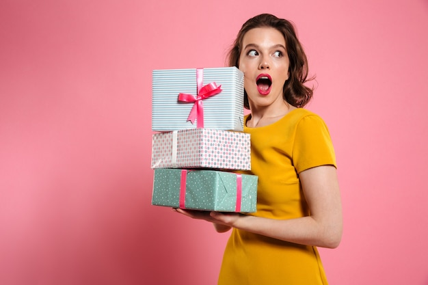 Retrato do close-up da menina bonita chocado com maquiagem brilhante, segurando a pilha de presentes, olhando de lado Foto gratuita