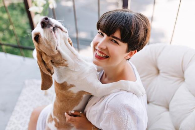 Retrato do close-up de cima da garota da risada, aproveitando a manhã na varanda com um animal de estimação engraçado. linda jovem de bom humor brincando com um cachorro beagle enquanto descansava após o jantar no terraço Foto gratuita