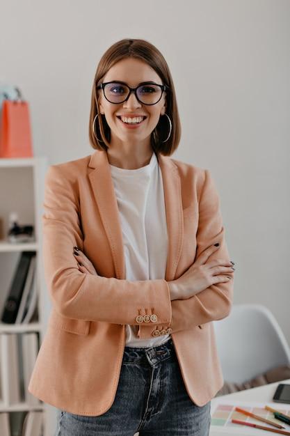 Retrato do close-up de mulher de negócios de cabelo curto sorridente em t-shirt branca, posando com os braços cruzados no escritório branco. Foto gratuita