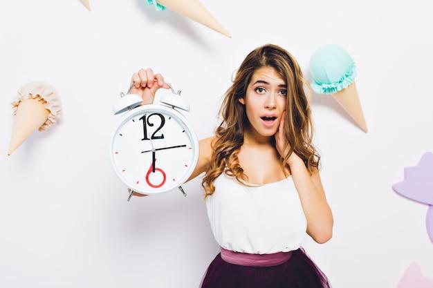 Retrato do close-up de mulher jovem e elegante em um vestido elegante, posando com relógio branco na parede decorada. menina de cabelos compridos e cacheados com expressão de rosto infeliz em frente à parede com sorvete Foto gratuita