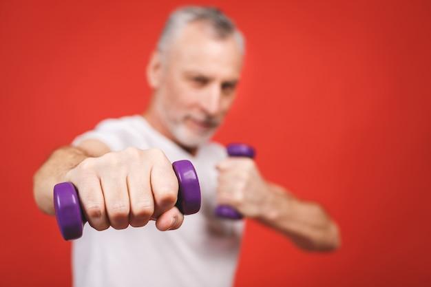 Retrato do close-up de um homem sênior que exercita com halteres. Foto Premium