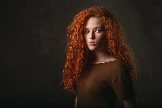 Retrato do close-up de uma jovem garota com cabelo ruivo cacheado em um vestido de cor cáqui Foto Premium