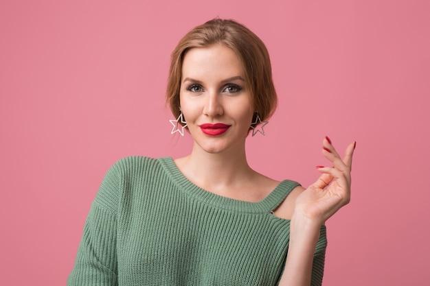 Retrato do close-up de uma jovem mulher sexy e atraente, maquiagem elegante, lábios vermelhos, suéter verde, modelo posando no estúdio, isolado, fundo rosa, brincos, olhando na câmera, segurando a mão, elegante Foto gratuita