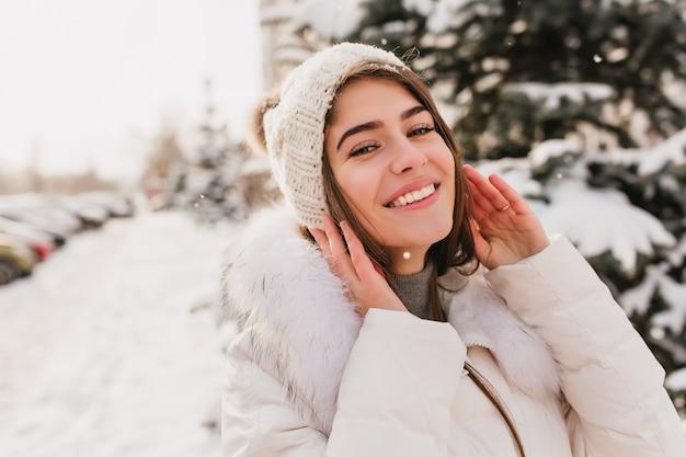 Retrato do close-up de uma linda mulher com olhos azuis, posando na rua em um dia nevado de inverno. foto ao ar livre da encantadora modelo feminina com chapéu de malha rindo Foto gratuita