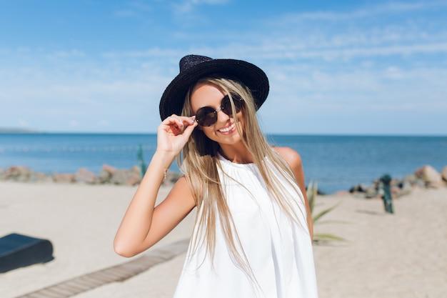 Retrato do close-up de uma menina loira e bonita com cabelo comprido está em pé na praia perto do mar. ela está sorrindo para a câmera. Foto gratuita