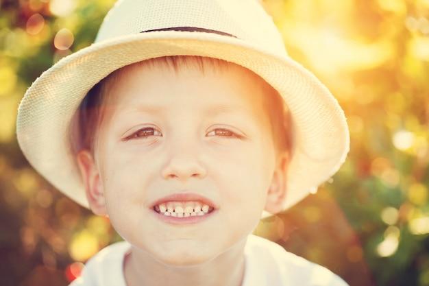 Retrato do close-up do menino de sorriso em um chapéu no dia de verão ensolarado. Foto Premium