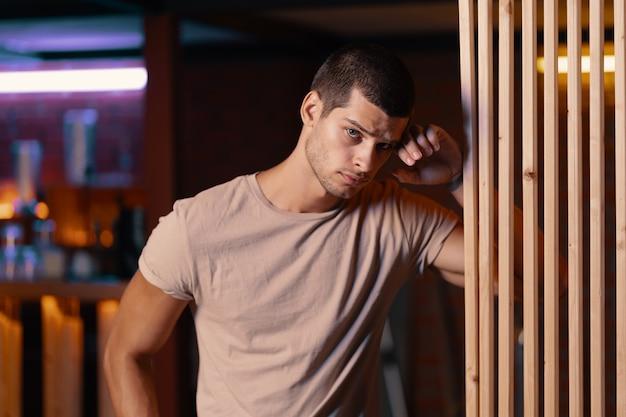 Retrato do close-up do modelo masculino atraente. jovem bonito em um bar Foto gratuita