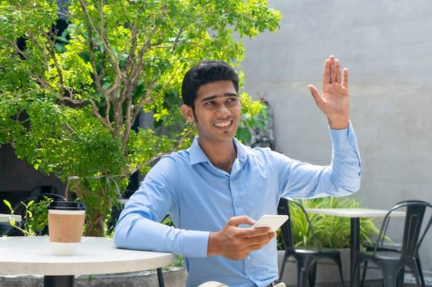Retrato do colega novo feliz do cumprimento do homem de negócios ao ar livre. Foto gratuita