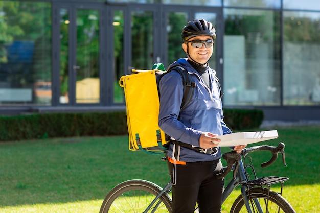 Retrato do correio de bicicleta com saco amarelo e bicicleta. homem de capacete e óculos, segurando a caixa de pizza Foto Premium
