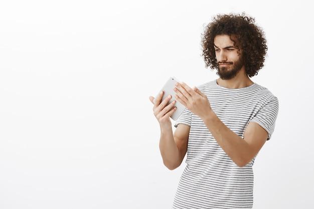 Retrato do designer masculino hispânico criativo com um corte de cabelo e barba elegantes, segurando o tablet digital e olhando para a tela, desenhando o plano de apartamento para criar o design Foto gratuita