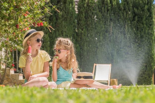 Retrato do duas meninas bonitos com sorvete. diversão no verão. Foto Premium