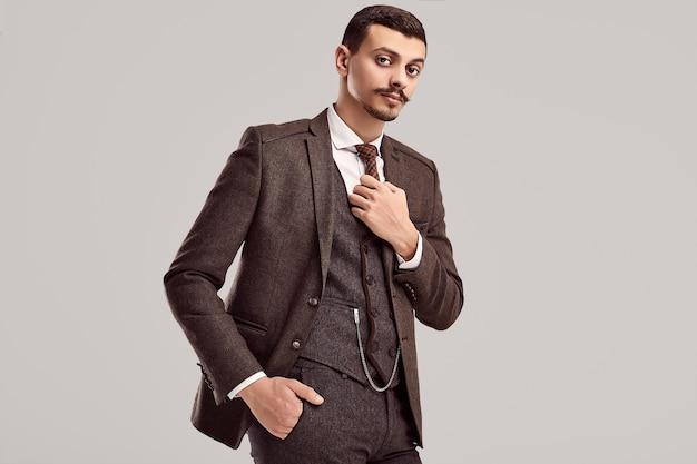 Retrato do empresário árabe confiante jovem bonito com bigode chique em terno completo marrom de lã no fundo do estúdio Foto Premium