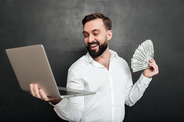 Retrato do empresário de sucesso na camisa branca, segurando o leque de notas de dólar de dinheiro e caderno de prata em ambas as mãos sobre cinza escuro Foto gratuita